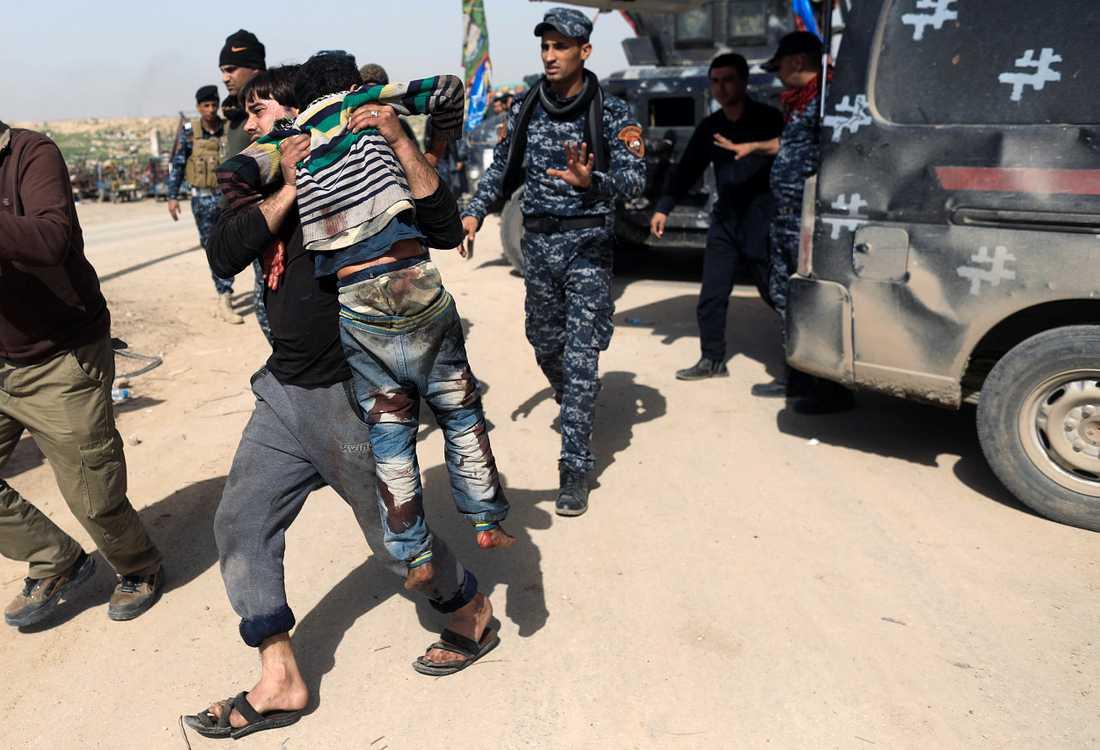 En man tar hand om en skadad anhörig i västra Mosul.