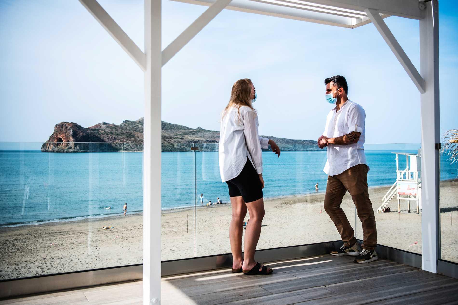 Reporter Matilda Aprea Malmqvist och Giorgos tittar ut över stranden från hotellet.
