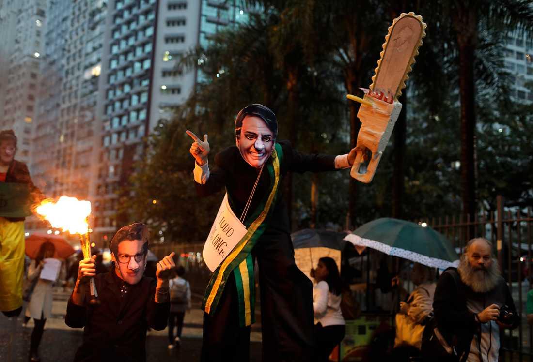 En demonstrant med Bolsonaro-mask och en låtsas-motorsåg protesterar i Rio de Janeiro till stöd för Amazonas.