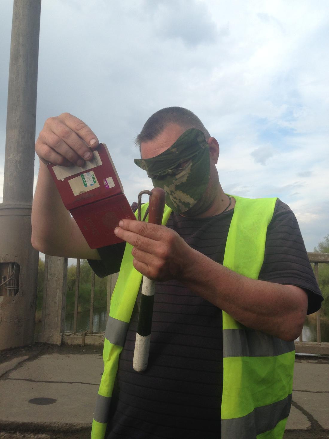 No passarán En maskerad lokal milisman inspekterar skribentens pass vid en checkpoint.