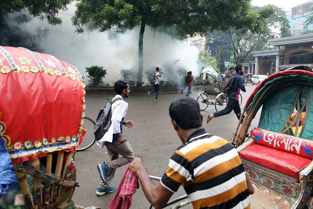 Studenter springer från polis som kastar tårgasbehållare.