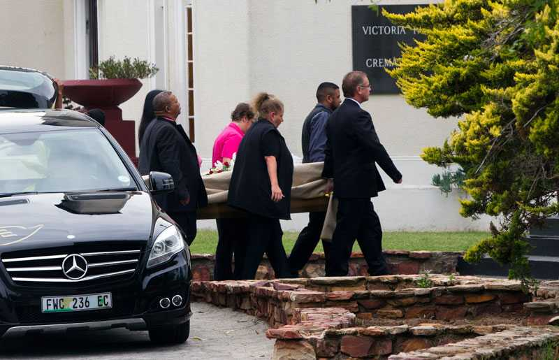 Samtidigt som häktesförhandlingarna begravdes Reeva Steenkamp. Här bärs kistan in till krematoriet.
