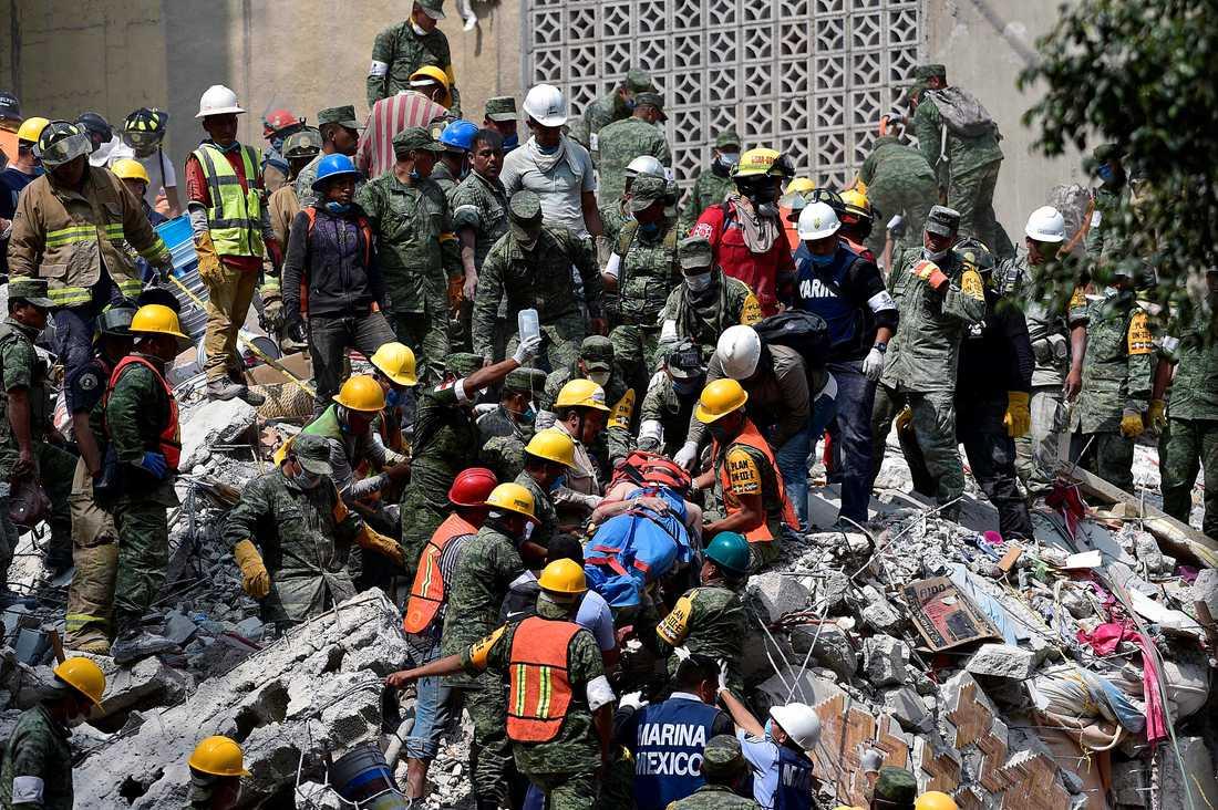 En man räddas ur rasmassorna i Mexiko City.