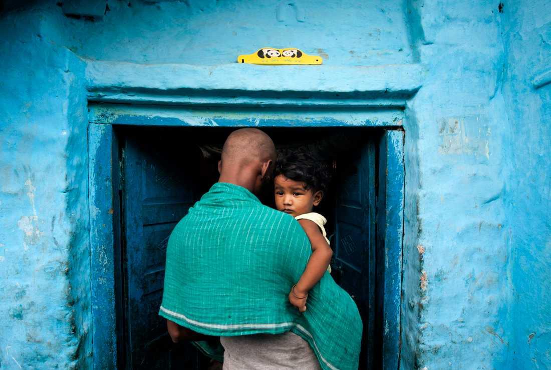En man bär på ett barn i New Delhi, Indien. Dödligheten bland barn under fem år över hela världen har minskat kraftigt under de senaste två årtiondena.