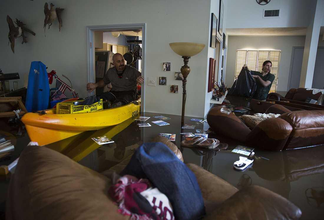 Larry Coser Jr och hans son Matthew försöker rädda värdesaker från Larrys fars hus efter att det svämmats över av vatten i Houston.