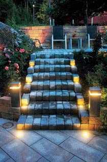 """Lys upp Vilket välkomnande! Gästerna får verkligen känna sig speciella när de går upp för trappan till altanen i den här trädgården. Punktbelysning i form av lysdiodslampor med varmt ljus på varannan trappavsats markerar trappan väl. Arrangemanget är trevligt och inbjudande. På var sida om trappan lyser pollare """"Stone Pillar"""" med infälld belysning från In-Lite upp området lite extra. De kostar runt 2 999 kronor."""
