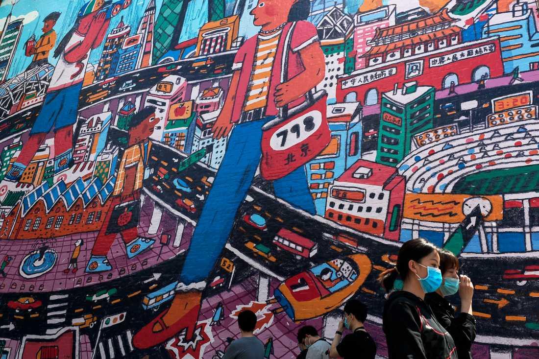 Kvinnor i ansiktsskydd promenerar förbi en målning i det berömda konstområdet 798 i Peking.