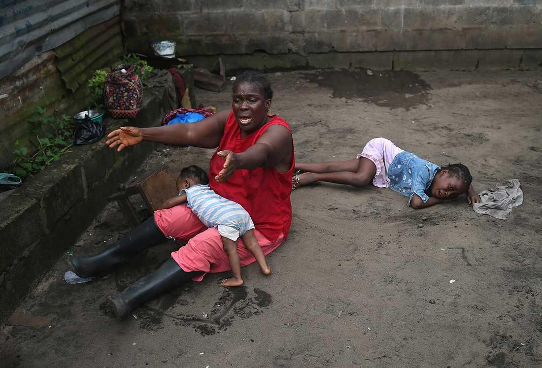 Sophia Doe sitter med sina barnbarn Beaty Mandi, 9 månader, och Arthuneh Qunoh, 9. Samtidigt ser hon personer komma för att föra bort dottern Mekie Nagbes kropp. Bilden är tagen i staden Monrovia i Liberia.