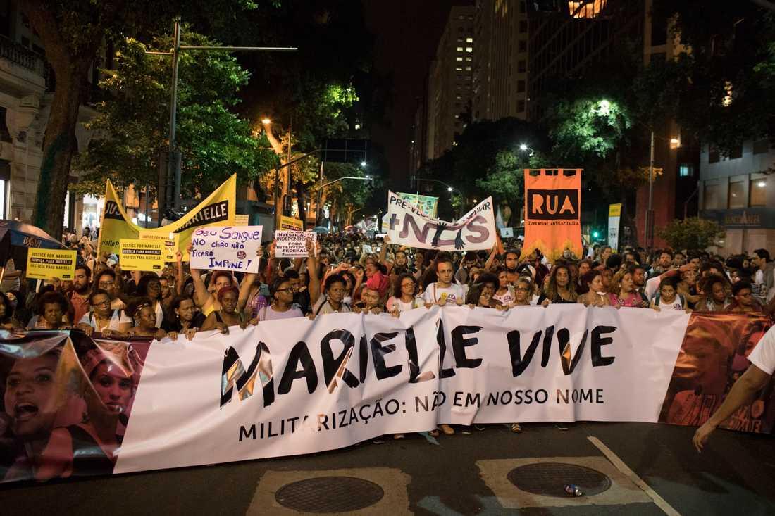 """Demonstranter håller flaggor med budskapet """"Marielle lever"""" under en demonstration i Rio några dagar efter mordet i mars 2018."""