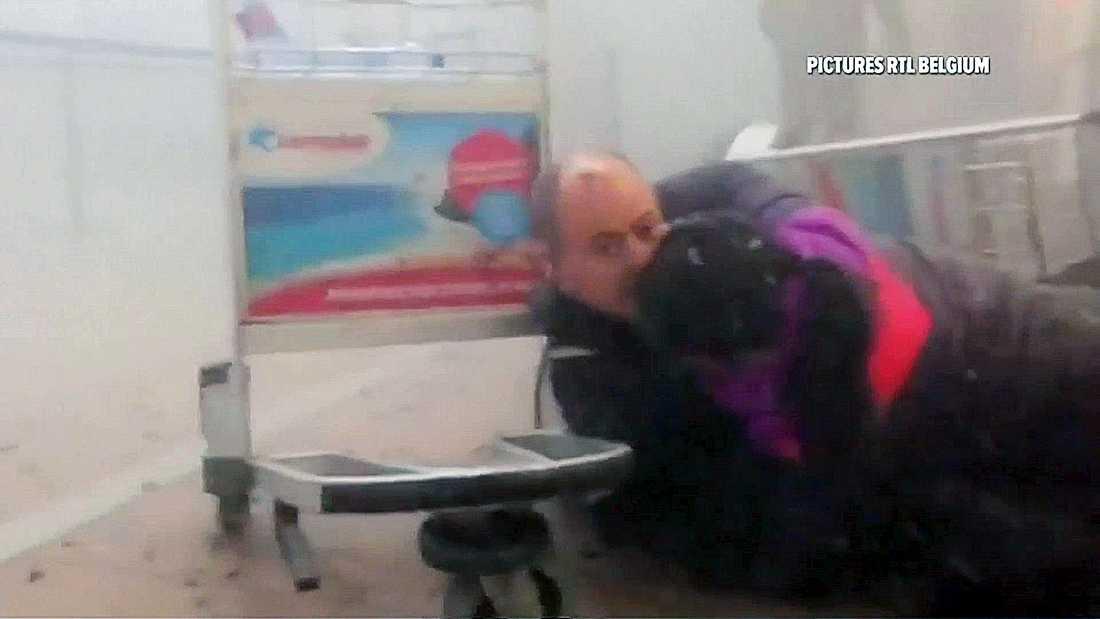 En man tar skydd efter terrorattack mot  Zaventemflygplatsen i Bryssel.