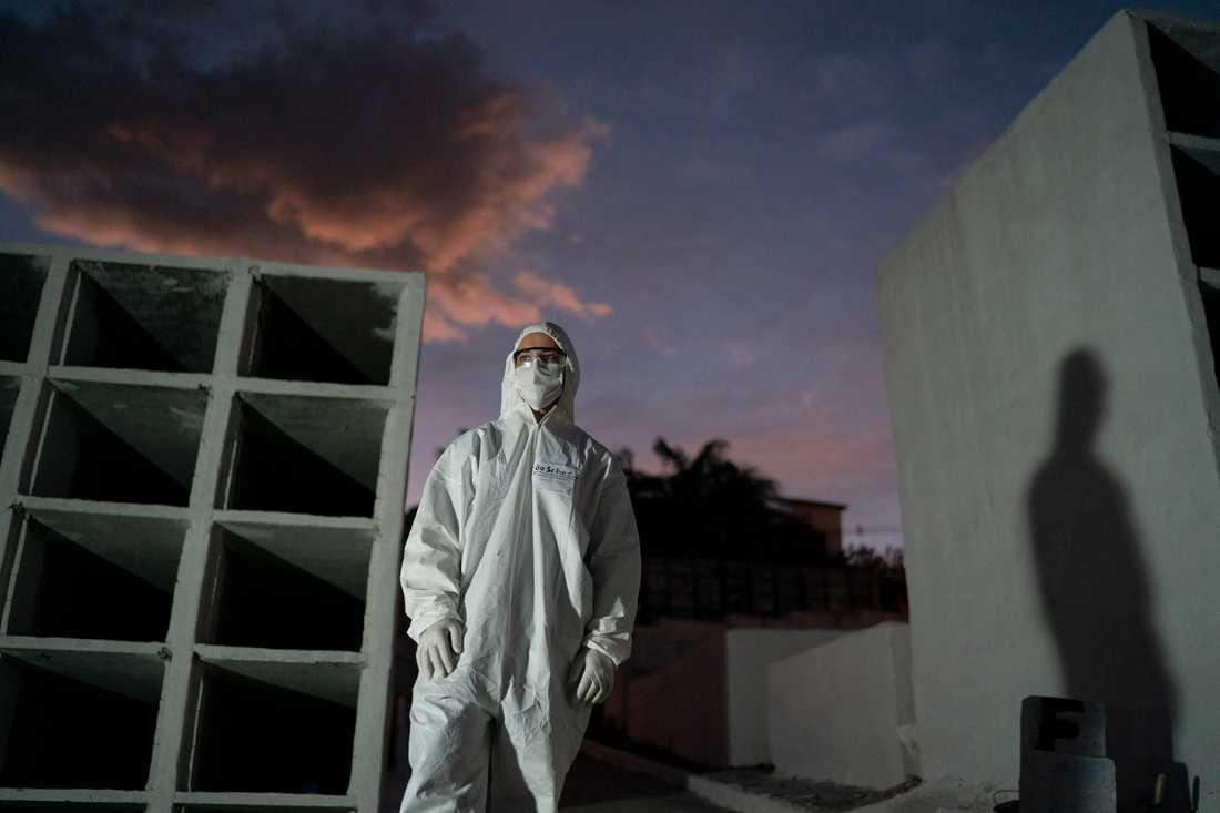 Kyrkogårdsarbetare i Brasilien iförd skyddsutrustning. Bild från 30 juni.