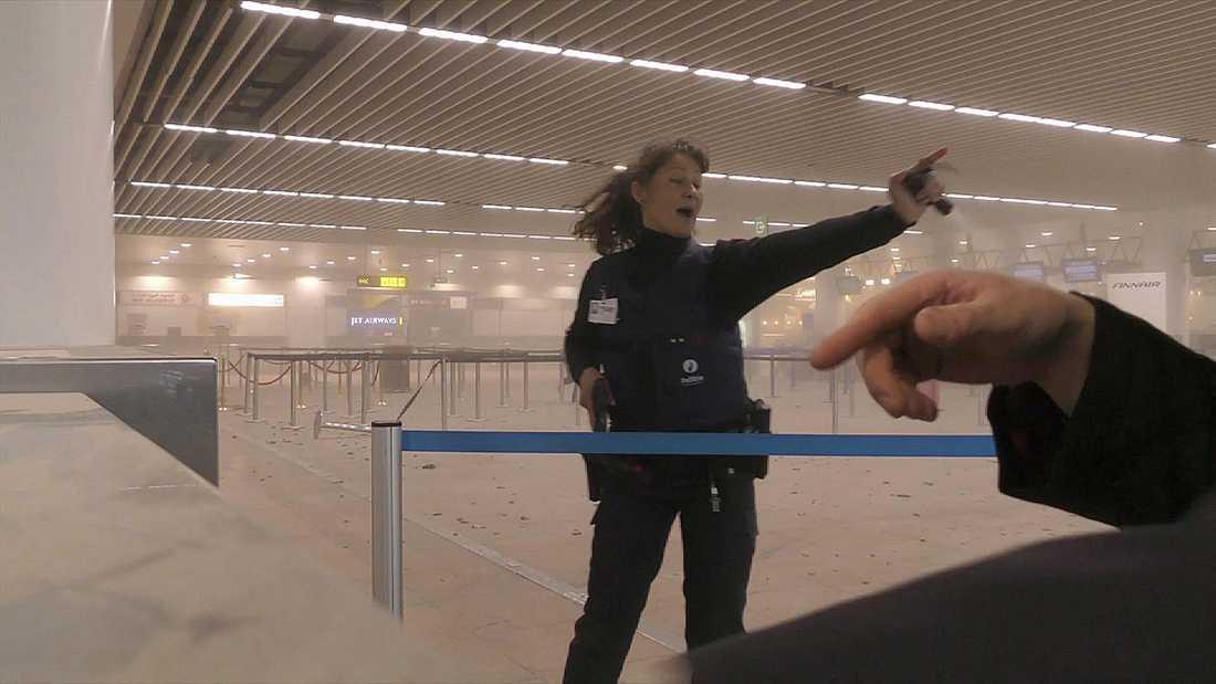 Polis med draget vapoen inne i en rökfylld flygplats i Bryssel