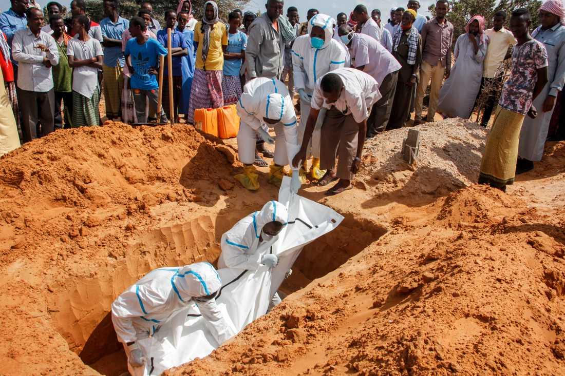 Vårdpersonal i skyddsutrustning vid en begravning av en man som dött i covid-19 på en begravningsplats i Somalias huvudstad Mogadishu.