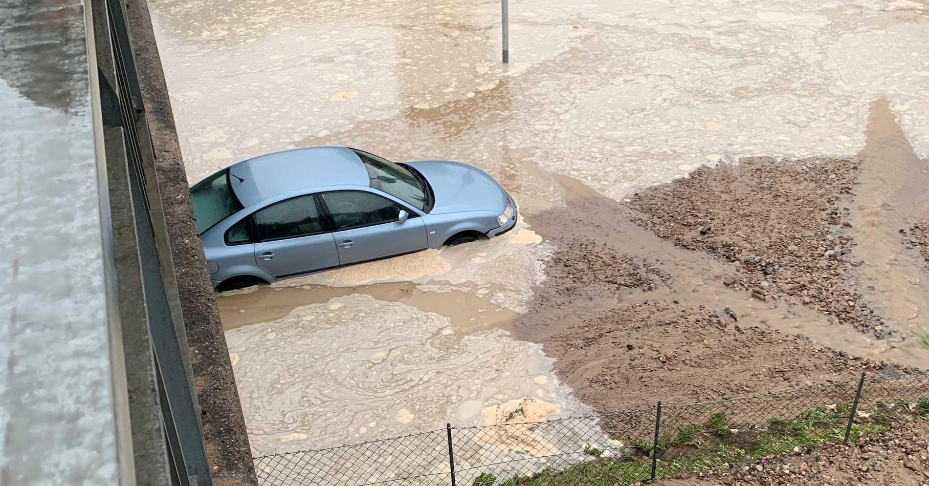 Bilder visar hur en bil står nästan helt under vatten på platsen.