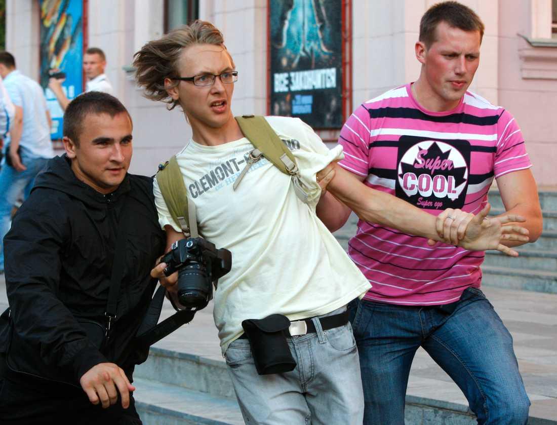 Belarus myndigheter slår ner allt hårdare på landets medier. På bilden griper en civilklädd polis en pressfotograf i Minsk den 20 juli.