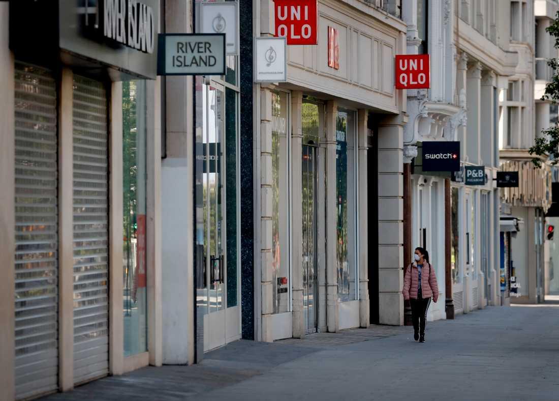 Den 23 mars stängde Storbritannien ner. På bilden en kvinna i ansiktsmask som går på den annars så trafikerade affärsgatan Oxford Street i London.