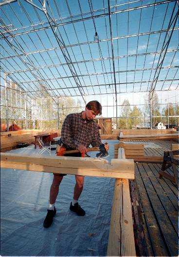 Anders Axelsson yxar till sin timmerstuga som han bygger i ett växthus. Enligt experter kommer han att spara 50 procent i energikostnader på att göra så här.