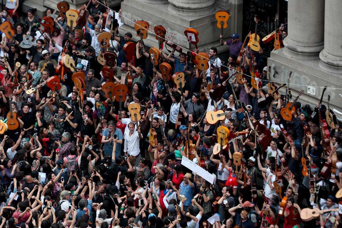 Demonstranter under en minnesceremoni i Santiago för musikern Victor Jara, som torterades och mördades 1973 under Augusto Pinochets militärdiktatur. Deltagarna sjöng Jaras sång El Derecho De Vivir En Paz (Rättigheten att leva i frid) – som blivit en av proteströrelsens samlande sånger.