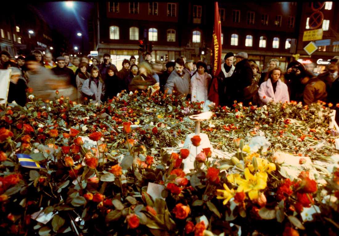 Sörjande människor lägger blommor på mordplatsen vid hörnet av Sveavägen och Tunnelgatan i Stockholm i mars 1986, för att hedra Sveriges statsminister Olof Palme som blev skjuten till döds på platsen. Arkivbild.