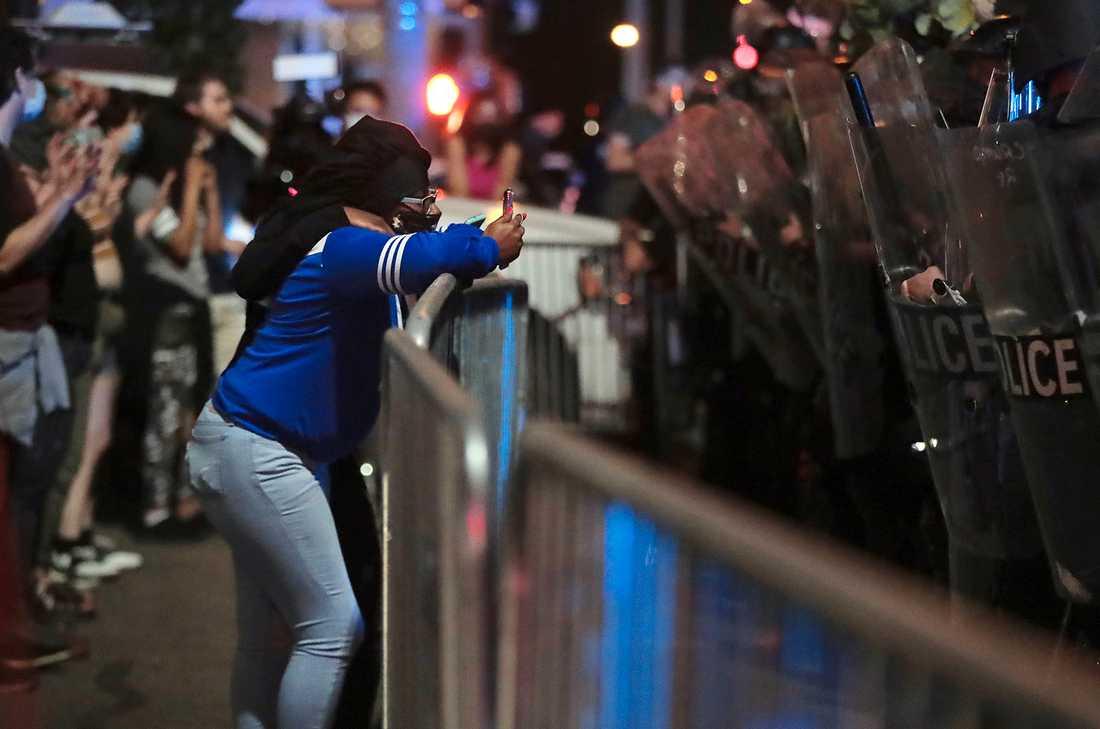 En demonstrant filmar kravallpolis under protesterna i Minneapolis då tusentals människor protesterade mot att en svart man brutalt dödats under ett polisingripande i staden.