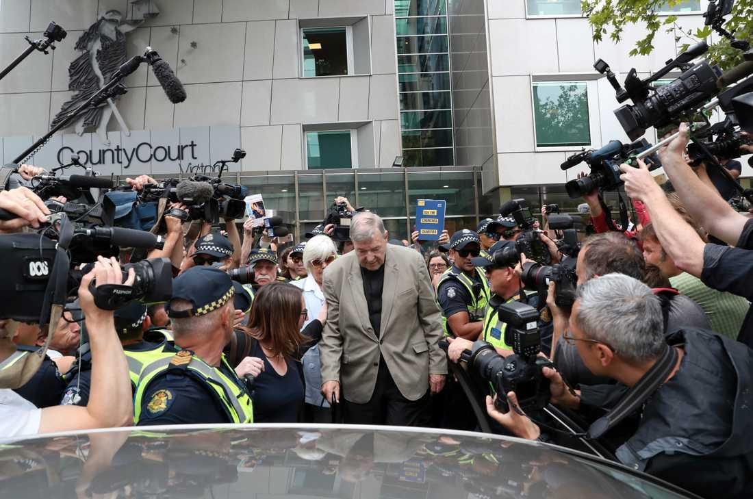"""Kardinal George Pell, 77, lämnar domstolen i Melbourne, Australien, medan demonstranter ropar """"monster"""" och """"ruttna i helvetet""""."""