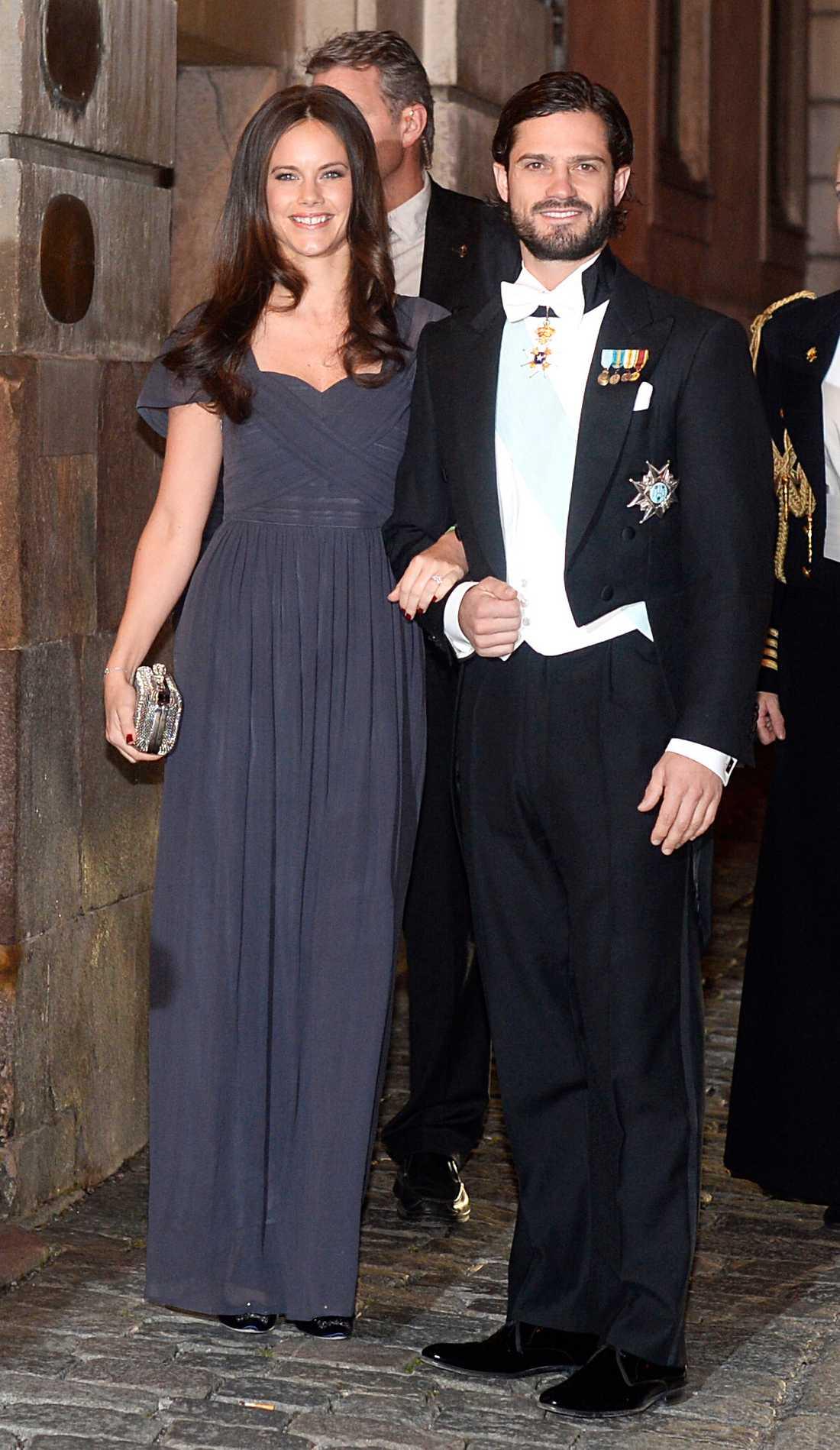 Sofia Hellqvist med sambo Carl Philip på Svenska Akademiens högtidssammankomst. Sofias midnattsblåa klänning med markerad midja matchar hennes hår perfekt.