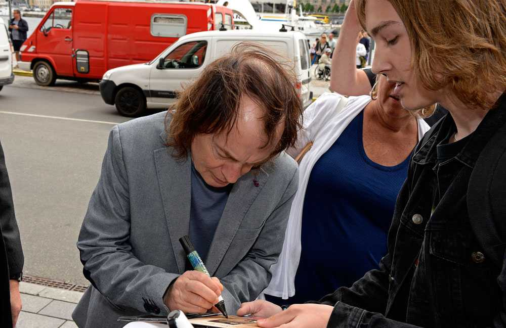 AC/DC har landat i Sverige. Angus Young skriver autografer utanför Grand Hotel.