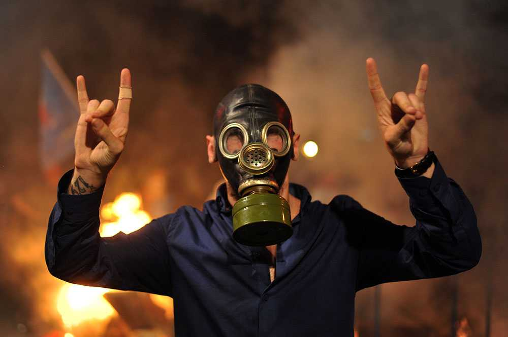 En demonstrant skriker slagord bakom sin gasmask i Istanbul. Tusentals samlades i staden för att protestera sedan en 22-årig demonstrant omkommit tidigare i veckan.