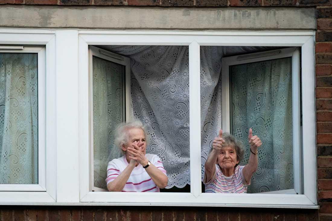 Två av de miljontals Londonbor som den senaste tiden varit begränsade till sina hem gör tummen upp för landets sjukvårdsservice NHS. Bilden från i början av maj.
