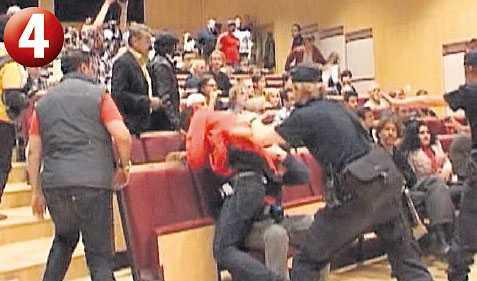 Det är väldigt oroligt i föreläsningssalen då flera försöker ta sig förbi poliserna.