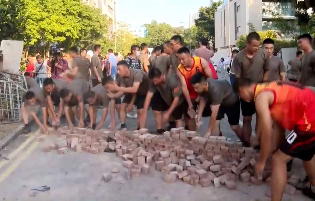 Kinesiska soldater plockar upp gatstenar från protesterna i Hongkong.