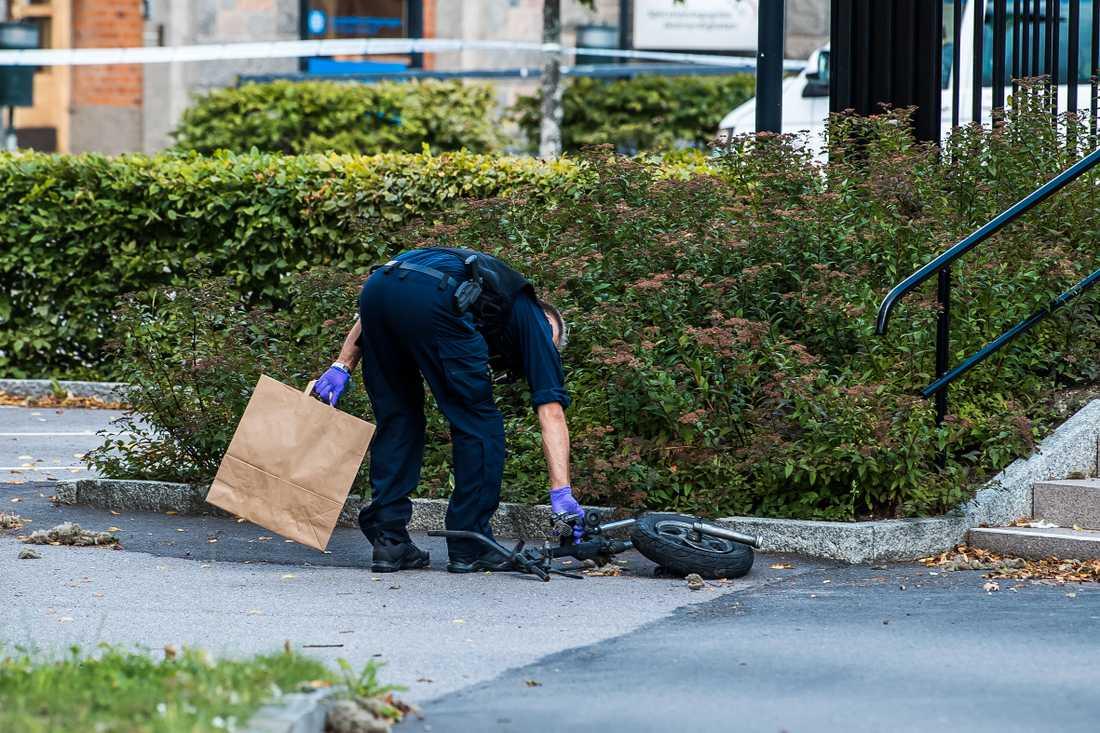 En polis plockar upp mopeddelar från gatan efter explosionen.