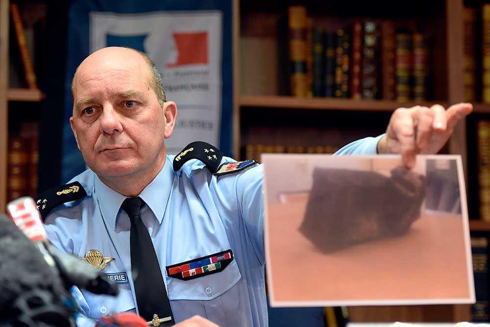 En utredare visar upp bilder av den förkolnade svarta lådan.