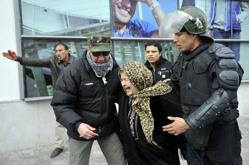 ÄLDRE KVINNA MITT I ATTACKEN En äldre tunisisk kvinna får hjälp att ta sig undan tårgasattacken i sammandrabbningarna mellan polis och demonstranter.