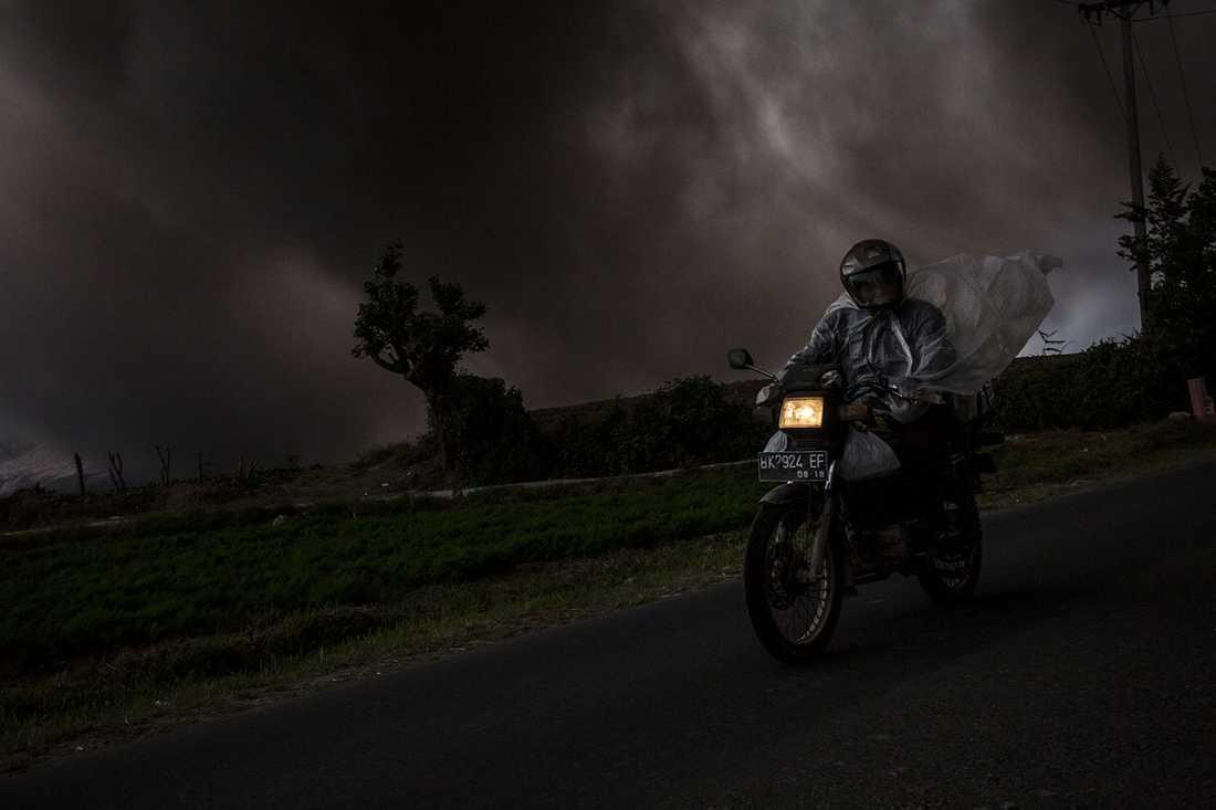 En man kör motorcykel genom tjock rök.