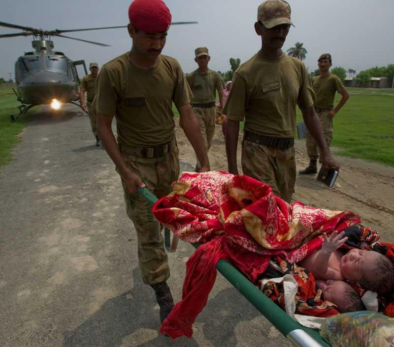 På väg i säkerhet. Mamma Zahida och de båda pojkarna transporteras från räddningshelikoptern. Den lilla familjen hade burits på en bår genom vatten som nådde upp till bröstkorgen.