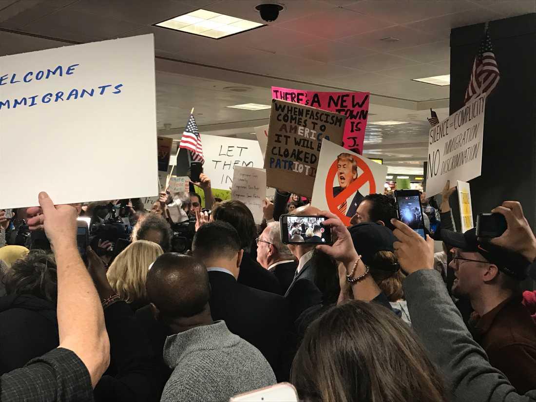Många av aktivisterna har skyltar med Trump-kritiska budskap och uppmaningar till solidaritet. Talkörer om öppna gränser ekar mellan väggarna.