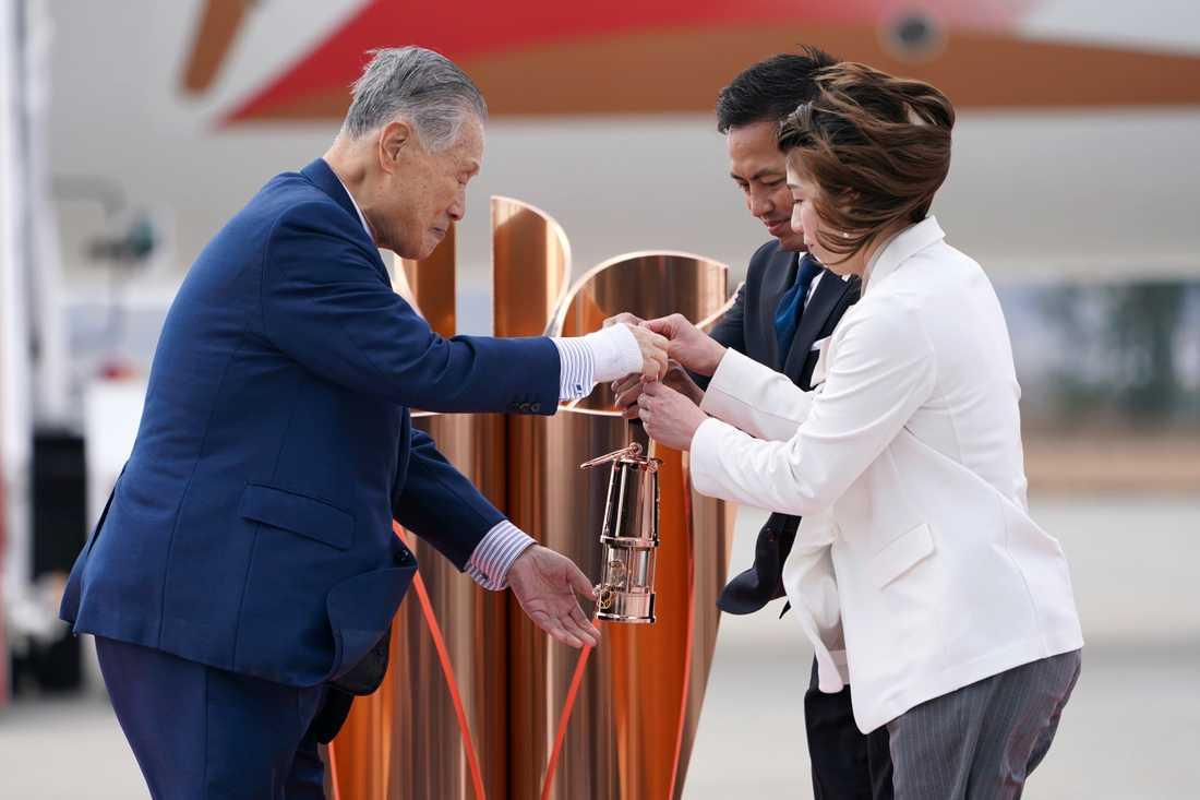 Tokyo 2020-chefen Yoshiro Mori tar emot den olympiska elden av de japanska OS-guldmedaljörerna Tadahiro Nomura och Saori Yoshida.