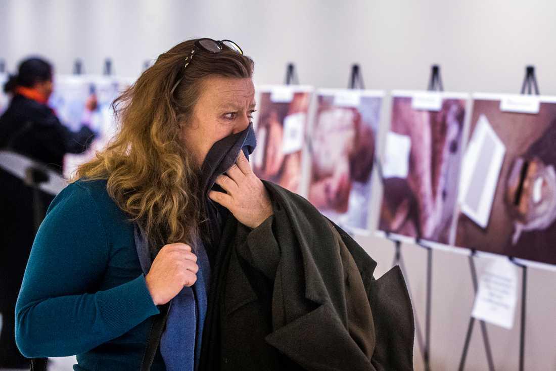 En kvinna reagerar på bilderna som visar tortyr och död från krigets Syrien.
