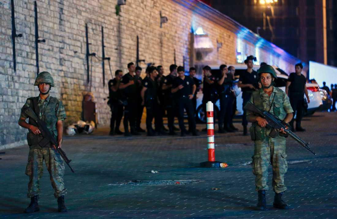Militär står vakt vid Taksimtorget i Istanbul, ett stort antal poliser hålls innanför avspärrningarna av oklar anledning.