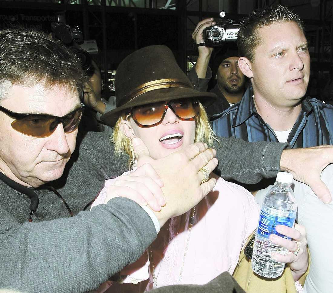 Jamie Spears är både Britneys pappa och förmyndare. han kontrollerar hennes liv in i minsta detalj. När Britney vill le in i kameran lägger han en hand över hennes mun.