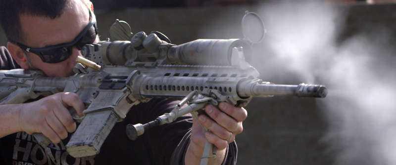 poserar med skjutvapen Krigsspelets producent Greg Goodrich poserar på bild med olika skjutvapen.