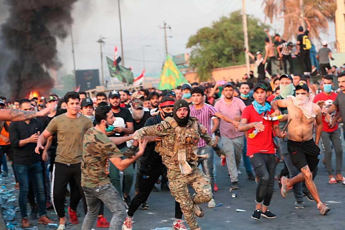 Enligt AP visar bilden en irakisk soldat som får hjälp av demonstranter att fly efter att ha misshandlats av andra demonstranter.
