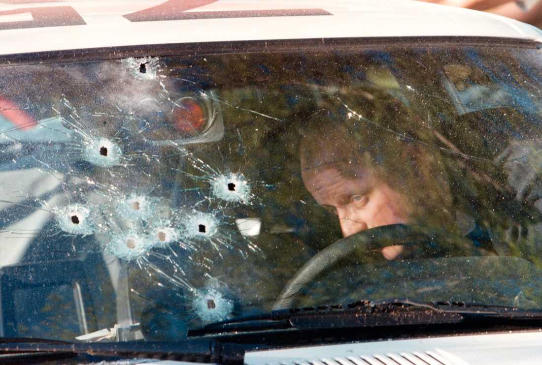 En brottstekniker undersöker en polisbil efter Malexandermorden.
