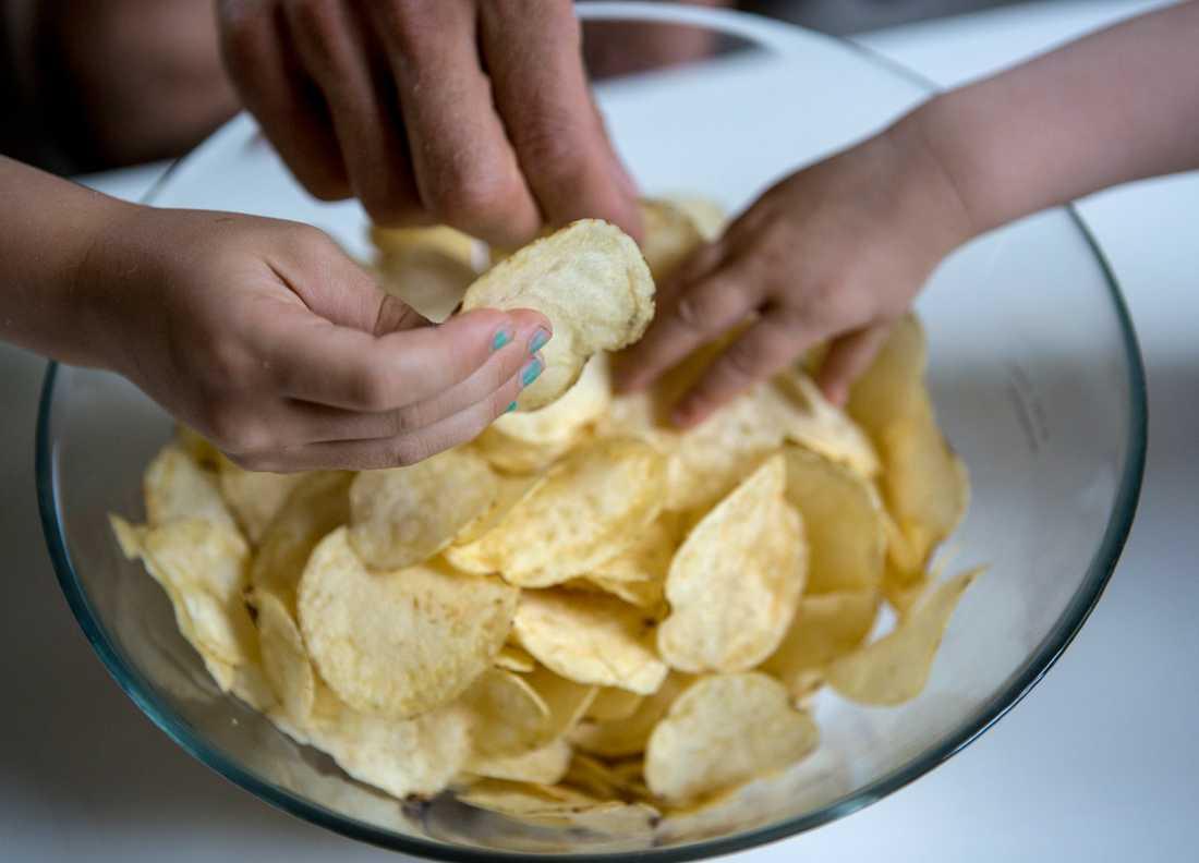 Händer som tar potatischips ur en stor glasskål. Arkivbild.