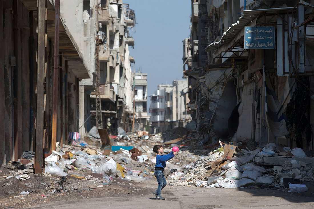 En pojke leker på gatan i staden Homs i Syrien.