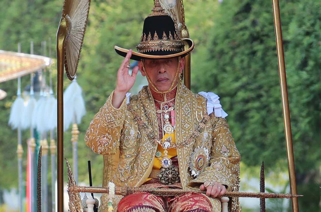Kung Rama X bar en bredbrättad hatt med en fjäder under processionen.