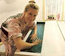 Aftonbladets reporter Agneta Elmegård sänker långsamt ner händerna i vattnet för att inte chocka fiskarna. Sedan börjar de putsa hennes hud mjuk och len.