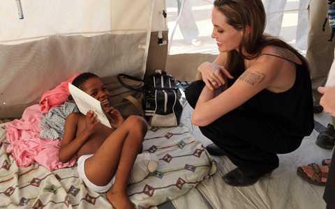 ANgelina Jolie pratar med en pojke som förlorade sitt vänstra ben i jordskalvet.