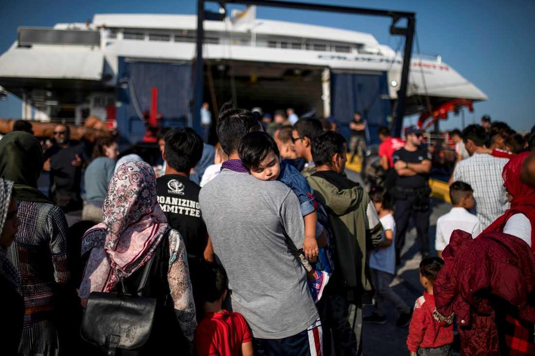 En man från Afghanistan bär sin dotter ombord en färja till fastlandet från Lesbos.